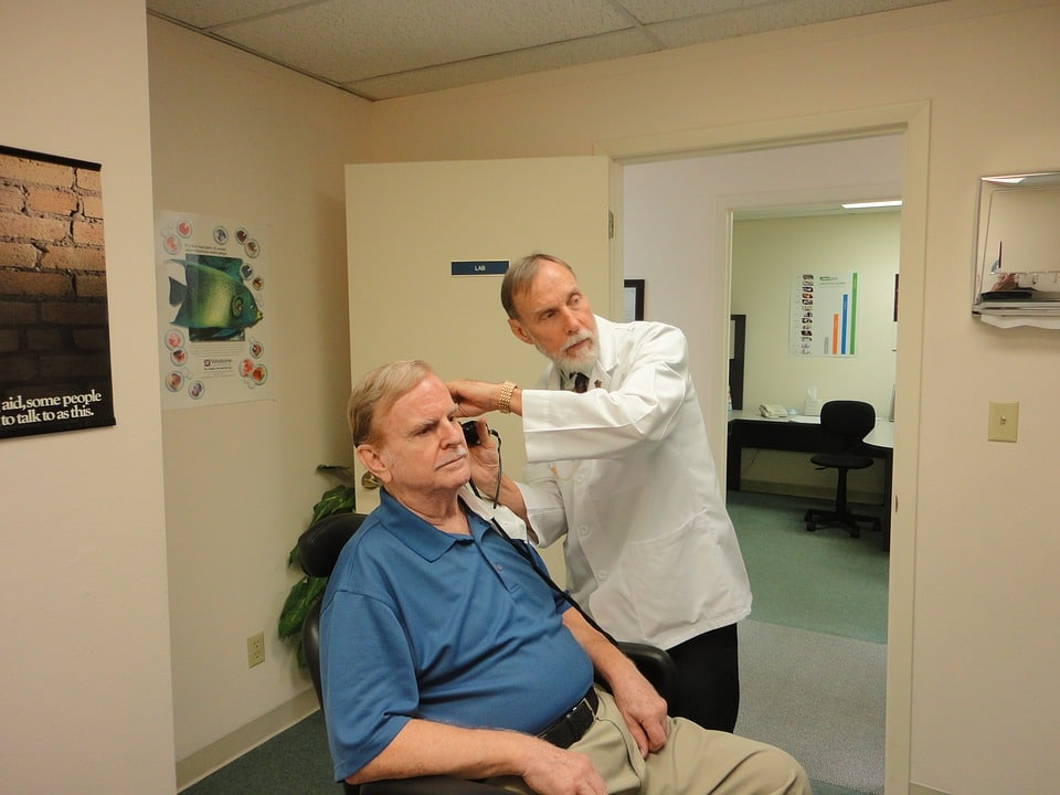 old man consults his doctor if he is have Otosclerosis or ear infection the doctor used a device to check the ear and seen in monitor
