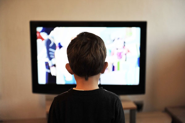 boy in black shirt watching tv