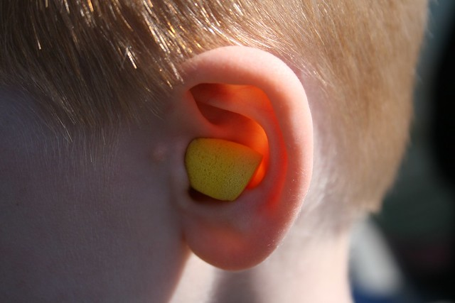 child wearing foam earplugs